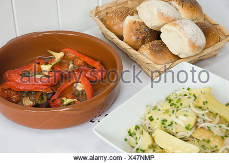 Potato and roast pepper dishes with bread rolls - Stock Photo