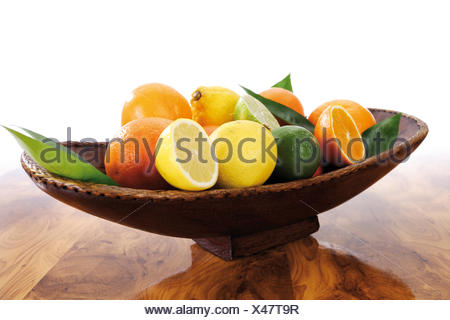 Citrus fruits in brown wooden bowl - Stock Photo