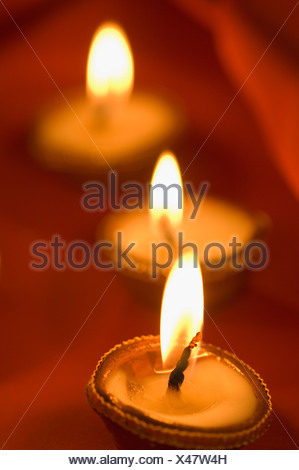 Close-up of a row of lit oil lamps - Stock Photo