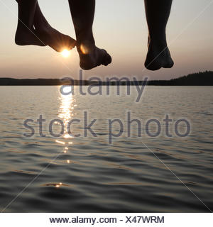 Legs dangling from a pier - Stock Photo