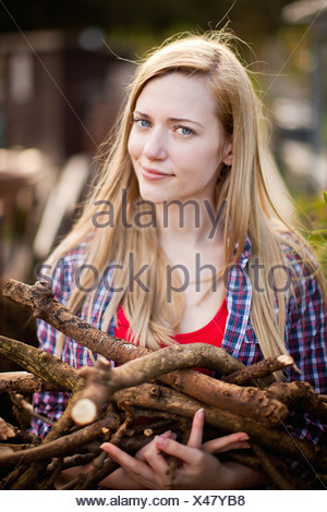 Woman gathering firewood in garden - Stock Photo