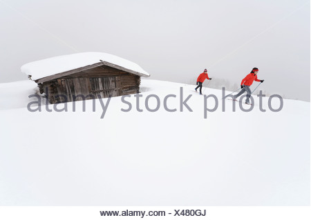 Italy, South Tyrol, Couple cross-country skiing, next to cabin - Stock Photo