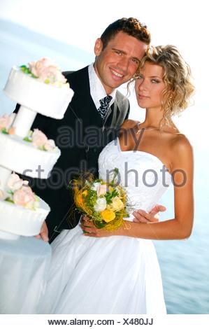 pridal couple outside with weddingcake - Stock Photo