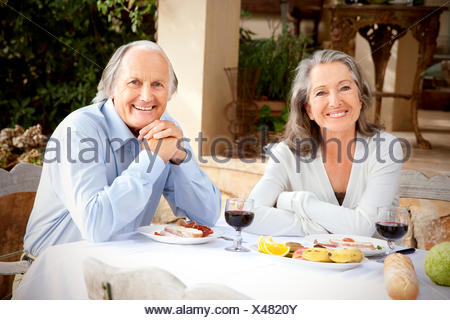 Spain, Mallorca, happy couple sitting at laid table in the garden - Stock Photo