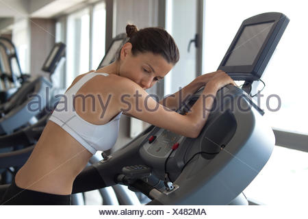 Woman using exercise machine in health club - Stock Photo