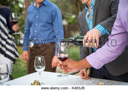Male hands pouring red wine at garden party table Stock Photo