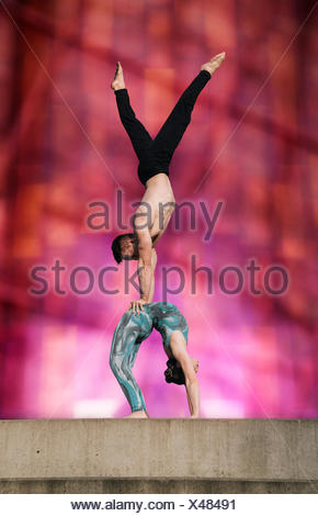 Teenage girl and young man, girl bent backwards in arch, man doing handstand on girls stomach - Stock Photo
