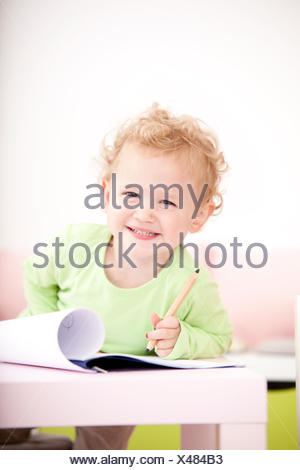 Portrait of grinning little blond girl with coloured pencil - Stock Photo