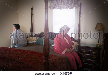 Mature couple sitting on opposite sides of bed - Stock Photo