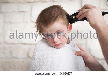 Boy getting a buzz hair cut by his father - Stock Photo