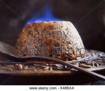 Flaming brandy Christmas pudding on wooden board - Stock Photo