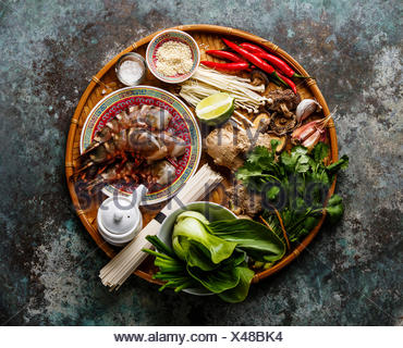 Ingredients for cooking Asian food with Tiger shrimps, udon noodles, mushrooms, greens, vegetables, spices on bamboo tray on metal background - Stock Photo