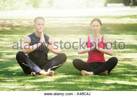 Young Couple Practicing Yoga - Stock Photo