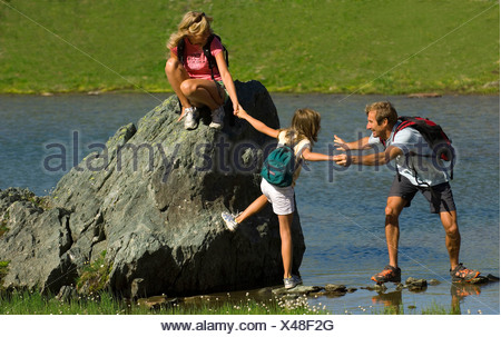 family crossing a lake in the French Alps, France, Alps - Stock Photo