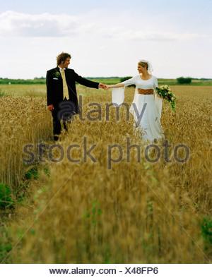Scandinavia, Sweden, Oland, Bride and groom walking in field - Stock Photo