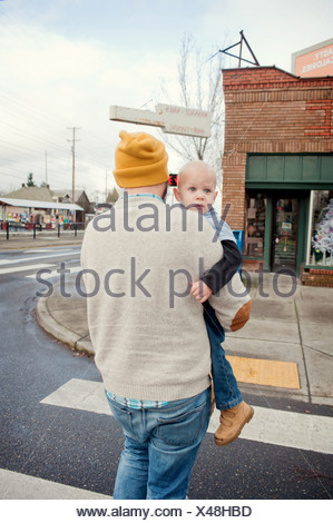Father carrying young son across pedestrian crossing - Stock Photo