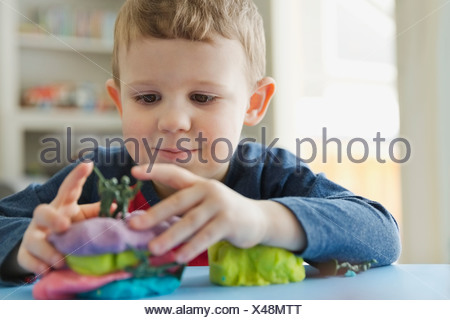 Boy playing with play dough at home - Stock Photo