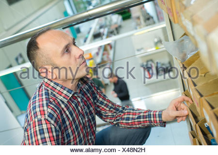 hardware store worker counting stock - Stock Photo