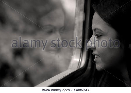 woman sitting on a train looking out of the window - Stock Photo