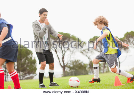 Coach training childrens soccer team - Stock Photo