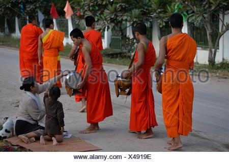 Buddhist monks walking along road to collect alms, Four Thousand island,South Laos,Southeast Asia. - Stock Photo