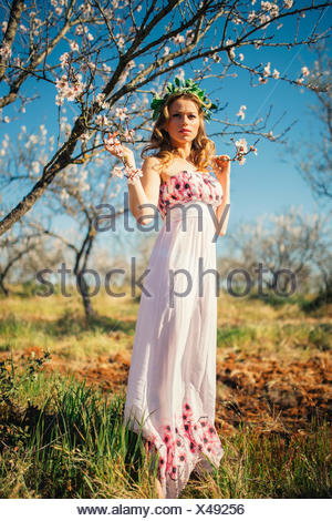Portrait of a woman wearing a headdress standing next to a blossom tree in spring - Stock Photo