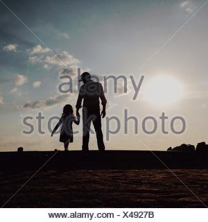 Silhouette Father With Daughter Standing On Field Against Sky