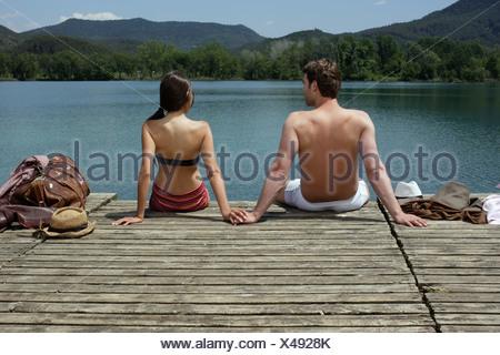 Couple sitting on dock - Stock Photo