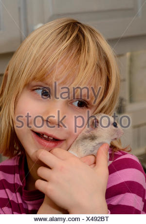 Girl, six years old, with a hamster, Ystad, Scania, Sweden - Stock Photo