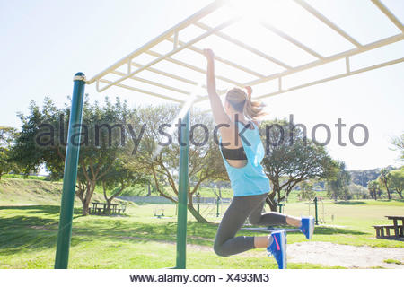 Woman training in park on monkey bars - Stock Photo