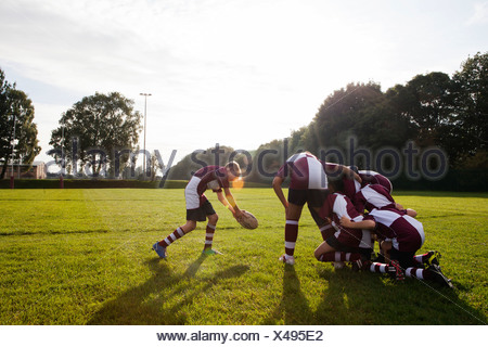 Teenage schoolboy rugby team taking ball from huddle - Stock Photo