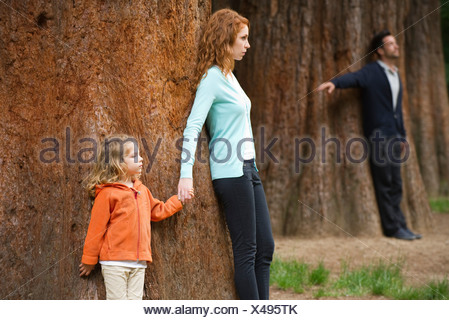 Mother and daughter leaning against tree, father standing separate in background - Stock Photo