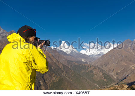 Photographer with yellow jacket taking a photograph of Mount Everest Mountain from Everest View Hotel viewpoint, Solo Khumbu - Stock Photo
