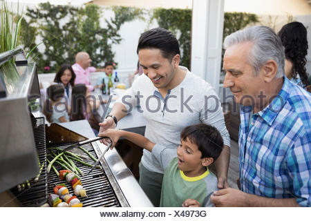 Multi-generation family barbecuing at grill on patio - Stock Photo