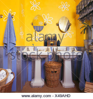 Stylised flowers drawn on wall above double pedestal basins in bright yellow and blue nineties bathroom - Stock Photo