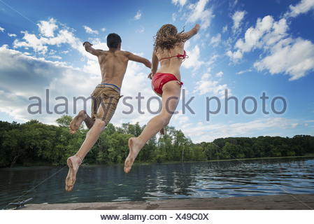 New York state USA boy and girl leaping off jetty into lake river - Stock Photo