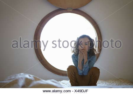 Portrait of sullen girl crouching in front of circular window - Stock Photo