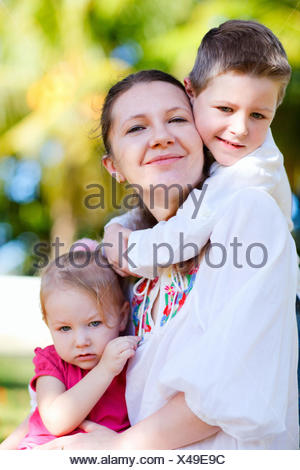 happy young mother outdoor with her little children snuggling up against her - Stock Photo