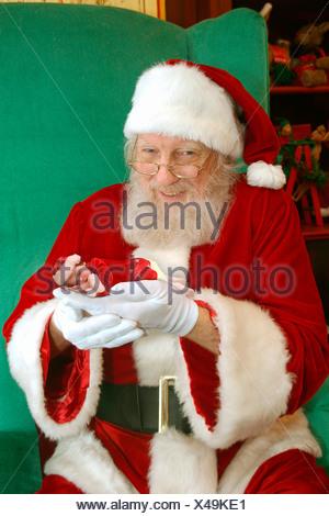 Santa holds baby. - Stock Photo