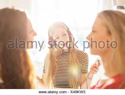 Teenage girls hanging out listening to music with headphones - Stock Photo