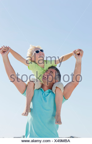 Happy father carrying son on shoulders - Stock Photo