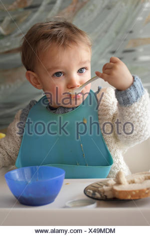 Portrait of baby boy (18-23 months) wearing baby bib eating at table - Stock Photo
