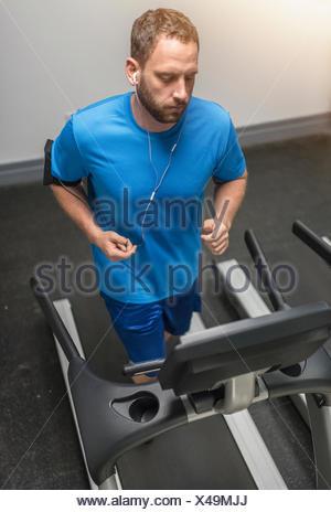 Mid adult man exercising on treadmill - Stock Photo