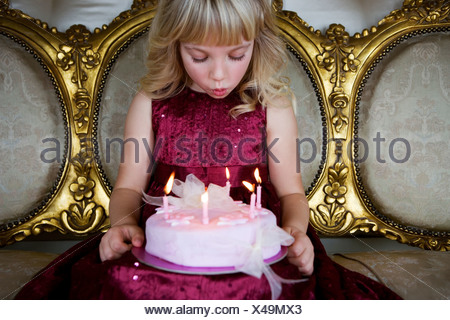 Little girl holding a birthday cake with lit candles - Stock Photo