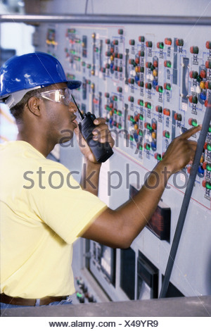 Mid adult man standing in the control room talking on a walkie-talkie - Stock Photo