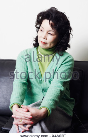Businesswoman sitting on a couch thinking - Stock Photo