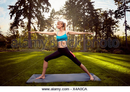 Mid adult woman practicing warrior pose in park - Stock Photo
