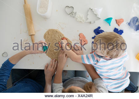 Overhead brothers and sister baking cookie cutters - Stock Photo