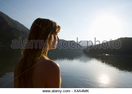 Blonde woman looks out across morning sunrise over lake - Stock Photo
