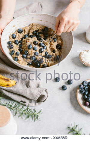 A woman's hands are photographed as she is mixing blueberry muffin batter. - Stock Photo